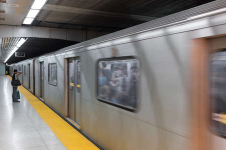 subway platform: Side view of a woman on subway platform looking at train passing through, Toronto, Ontario, Canada