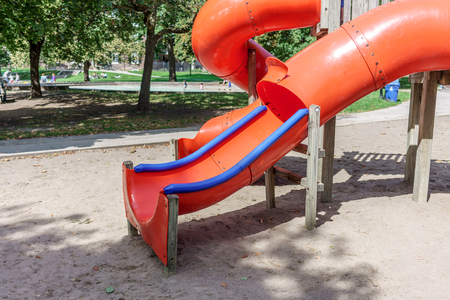 incidental people: Red slide in a playground, Toronto, Ontario, Canada Stock Photo