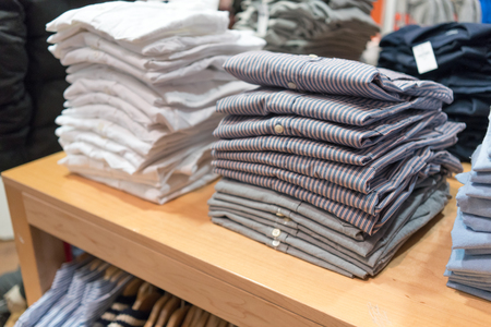 Stacks of shirts in clothes shop