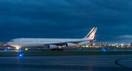 western script: Airplane standing on runway at airport in night Editorial