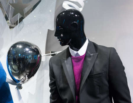 male likeness: Mannequins wearing suit and sweater in a clothing store