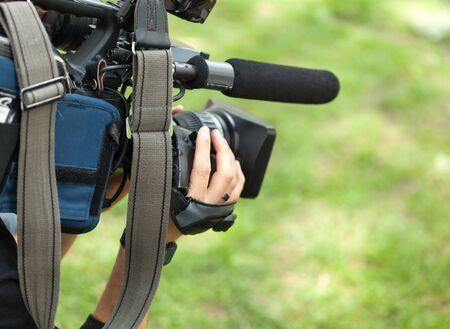 unrecognisable person: Cameraman filming with video camera Stock Photo