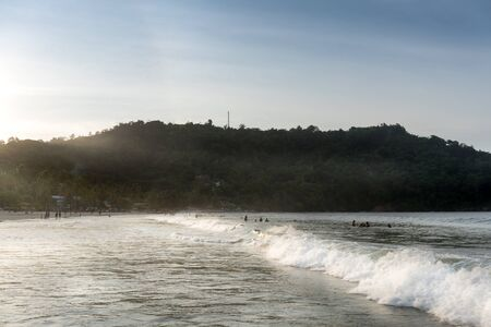 unrecognisable person: Tourists at beach during sunset, Trinidad, Trinidad And Tobago Stock Photo