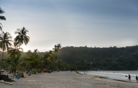 Tourists at beach during sunset, Trinidad, Trinidad And Tobago Imagens