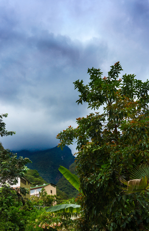 cusco region: Houses at beneath of mountain range against cloudy sky, Machu Picchu, Cusco Region, Urubamba Province, Machupicchu District, Peru Stock Photo