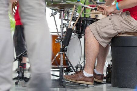 low section view: Low section view of a man playing drum with drum sticks