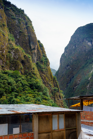cusco province: Houses at beneath of mountain range against sky, Machu Picchu, Cusco Region, Urubamba Province, Machupicchu District, Peru