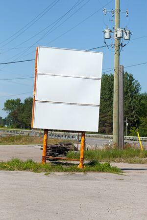 electricity pylon: Empty billboard with electricity pylon at roadside Stock Photo