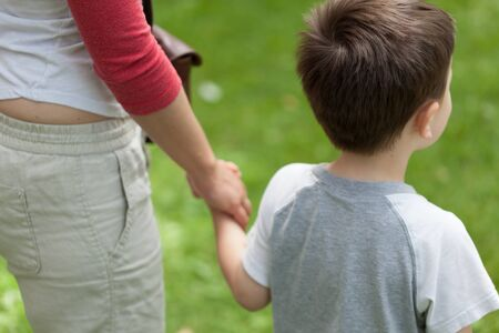 midsection: Mother and son standing with holding hands in park