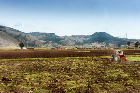 ploughing: Tractor ploughing field with mountain range in background, Cusco, Peru Stock Photo