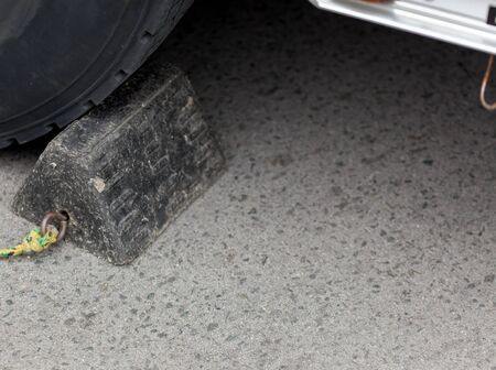 chock: Close-up of chock beneath a car tyre