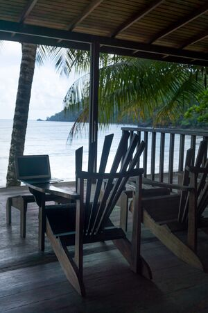 away from it all: Laptop on Adirondack chair at a tourist resort and sea viewed through tourist resort, Trinidad, Trinidad and Tobago