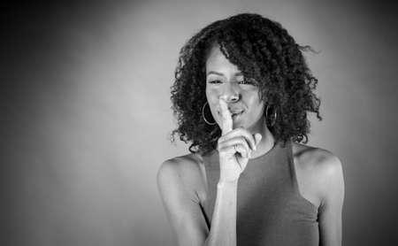 guardar silencio: mujer atractiva en el fondo plein un disparo en estudio con luces suaves con una expresión interesante y dramática iluminación Negro y negro, b & w Foto de archivo