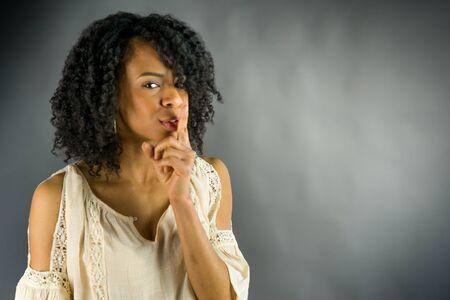 guardar silencio: mujer atractiva en el fondo plein un disparo en estudio con luces suaves con una expresión interesante y dramática iluminación