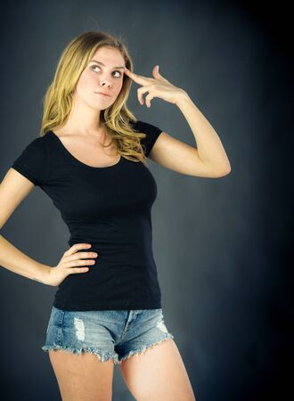 attractive woman on plein background shot in studio with soft lights with an interesting expression and dramatic lighting Stock Photo