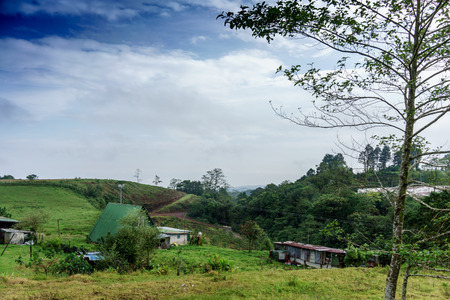 tranquillity: Colour Image, Photography, Day, Outdoors, No People, Horizontal, Sky, Tranquillity, Nature, Rural Scene, Tranquil Scene, Scenics, Green, Cloud - Sky, Architecture, Built Structure, House, Building Exterior, Hut, Hill, Landscape, Old-fashioned, Weathered,  Stock Photo