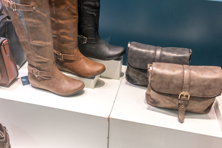 medium group of people: Photography, Indoors, No People, Low Angle View, Leather, Purse, Boot, Display, For Sale, Medium Group Of Objects, Still Life, Brown, Horizontal, Colour Image, Fashion, Handbag, Bag, Personal Accessory, Elegance, Glamour, Close-up, Footwear, Shop Window,