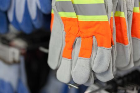 consumerism: Close-up, Colour Image, Conformity, Construction Industry, Consumerism, Differential Focus, For Sale, Glove, Hanging, Horizontal, Indoors, Merchandise, No People, Orange, Photography, Protection, Protective Workwear, Retail, Safety, Shop, Work Glove