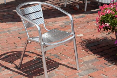 Absence, Armchair, Botany, Chair, Cobblestone, Colour Image, Day, Empty, Flower, Fragility, Front Or Back Yard, Furniture, Horizontal, Man Made Object, Metal, Metallic, No People, Outdoors, Pavement, Photography, Shadow, Silver Coloured, Single Object, St