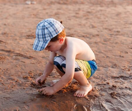 about age: 4-5 Years, Barefoot, Baseball Cap, Beach, Beach Holiday, Carefree, Casual Clothing, Caucasian Appearance, Child, Children Only, Colour Image, Crouching, Curiosity, Cute, Day, Enjoyment, Full Length, Fun, Innocence, Joy, Leisure Activity, Lifestyles, Makin Stock Photo