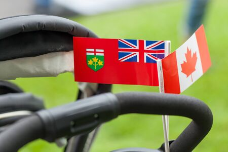 three objects: Pram, Pushchair, Handle, Still Life, Three Objects, Black, Baby Equipment, Differential Focus, Canadian Flag, White, Maple Leaf, Horizontal, Traditionally Canadian, Pride, Respect, Colour Image, Photography, Outdoors, Day, National Flag, Red, Patriotism,  Stock Photo