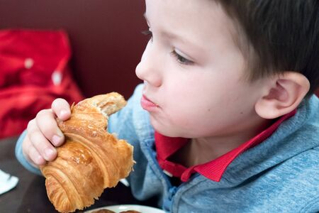 only one boy: People, Photography, Indoors, One Person, 6-7 Years, Child, One Boy Only, Only Boys, Children Only, Males, Primary Age Child, Childhood, Horizontal, Eating, Croissant, Healthy Eating, Healthy Lifestyle, Looking Away, Holding, Headshot, Differential Focus, Stock Photo