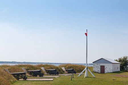 Photography, Outdoors, No People, Colour Image, Horizontal, Cannon, Canadian Flag, History, Metal, Security, In A Row, Weaponry, Repetition, Hut, Architecture, Built Structure, Building Exterior, Field, Victoria Park, Charlottetown, Prince Edward Island,