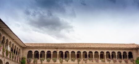colour image: Arch, Architectural Column, Architecture, Building Exterior, Built Structure, Cathedral, Catholicism, Christianity, Church, Cloud - Sky, Colonnade, Colour Image, Corridor, Cusco City, Day, Flower, History, Horizontal, La Compania, Low Angle View, No Peopl