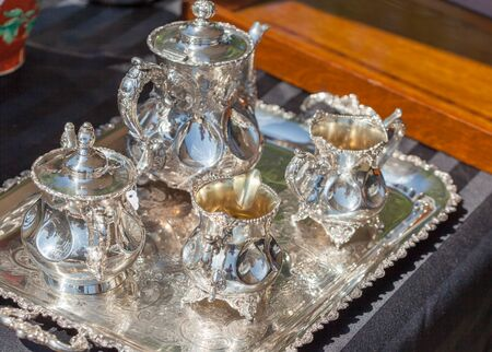 four objects: Luxury, Elegance, Silver Coloured, Tray, Group Of Objects, Cup, Man Made Object, Shiny, Crockery, Expense, Tea Cup, Teapot, Silver - Metal, Differential Focus, No People, Four Objects, Close-up, Horizontal, Colour Image, Photography, Indoors, Still Life,  Stock Photo