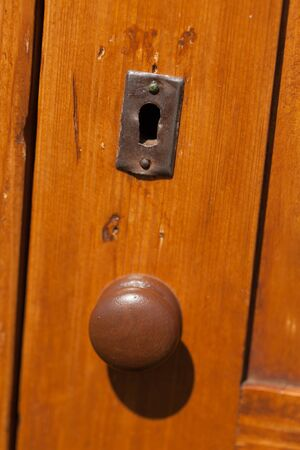 colour image: Full Frame, Backgrounds, Vertical, Outdoors, Day, No People, Photography, Colour Image, Differential Focus, Wood - Material, Brown, Old, Close-up, Doorknob, Metal, Handle, Keyhole, Part Of, Textured, Circle, Metallic, Doorway, Front Door, Entrance, Privac Stock Photo