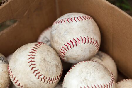medium group of people: Baseball - Ball, Ball, Sport, White, Dirty, Medium Group Of Objects, Colour Image, Photography, Red, Stitching, Baseball - Sport, Group Of Objects, Thread, Differential Focus, Box - Container, Cardboard Box, Cardboard, Close-up, Still Life, No People, Hor