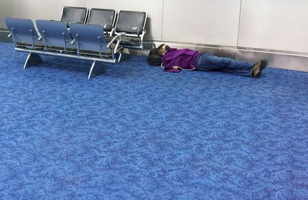 floo: Photography, Indoors, Chair, Waiting Room, In A Row, Seat, Colour Image, Horizontal, Flooring, Simplicity, Airport, Airport Departure Area, Travel, Metal, Blue, One Person, Sleeping, Resting, Lying On Back, Lying Down, Unrecognizable Person, Lying On Floo