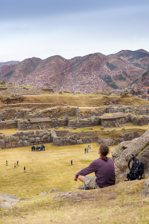 colour image: Ancient, City, Colour Image, Cusco City, Day, Distant, Hill, History, Inca, Landscape, Looking At View, Men, Mountain, Mountain Range, Old Ruin, On Ground, Outdoors, Peru, Peruvian Culture, Photography, Physical Geography, Rear View, Road, Sacsayhuaman, S Stock Photo