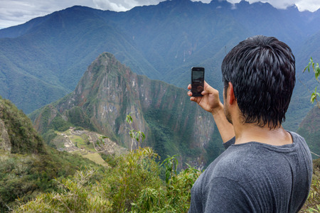 Getting Away From It All, Tourist, Looking At View, Men, Lifestyles, Leisure Activity, One Man Only, One Person, Solitude, Unrecognisable Person, The Andes, Rear View, Photographing, Photography Themes, Holding, Mobile Phone, Using Phone, Technology, Wire