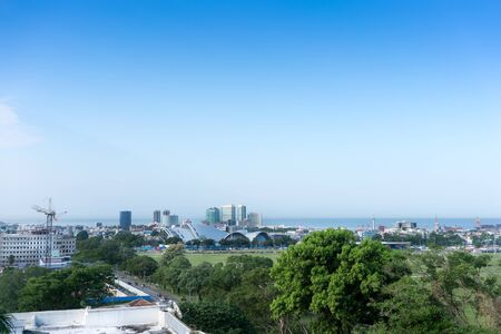 colour image: Colour Image, Photography, Day, Outdoors, No People, Horizontal, Clear Sky, Architecture, Building Exterior, Built Structure, City, Cityscape, Sea, Horizon Over Water, Tree, Elevated View, Port Of Spain, Skyscraper, Skyline, Office Block Exterior, Crane,