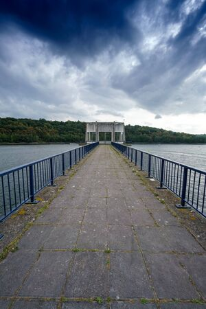 Empty pier and railings with diminishing perspective, clouds in sky, Belgium. belgium europe