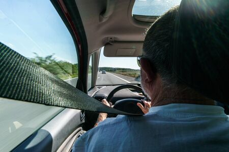 Rear view of man driving car, view over shoulder with seat belt. belgium europe