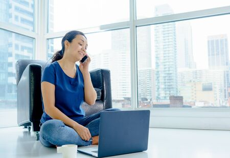 cross legged: Woman sitting indoors on floor, with laptop using mobile phone. asian, long hair, adult Stock Photo
