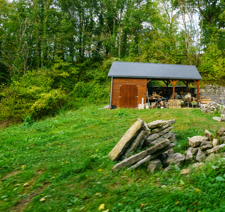 Merveilleux Small Wooden Hut With Trees Behind, Piles Of Rocks In Foreground. Belgium  Europe Stock