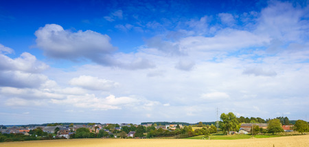Panoramic shot of field with distant buildings and clouds, Belgium. belgium europe