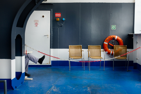 Empty chairs and lifebuoy in ship; Greece