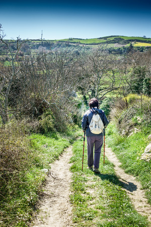 Rear view of woman hiking on country road Crete Greece Europe