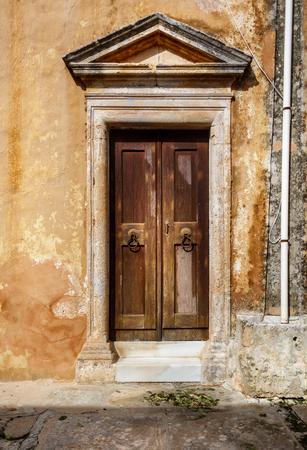 Front view of wooden door with door knockers Crete Greece Europe
