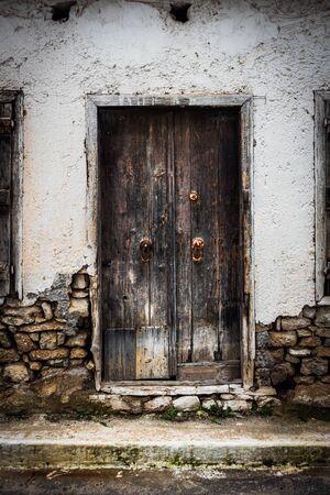 Weathered wooden door with door knob and stone wall