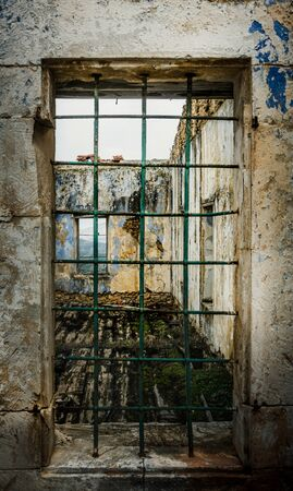 View of ruined structure through rusty iron bars