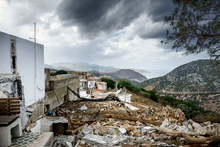 Old residential buildings with demolition debris and mountain against cloudy sky, Crete, Greece
