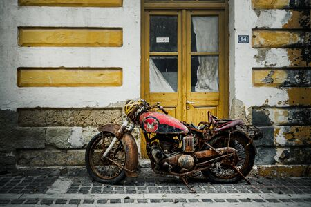 Old rusty motorbike in front of house