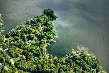 Aerial view of house amidst trees by lake, Canada