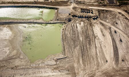 Aerial view of vehicle at construction site by pond, Canada