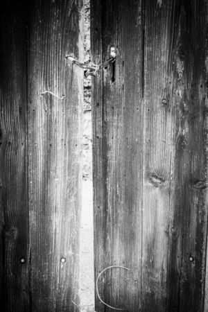 Full frame view of old wooden door with metal chain